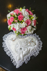 Two rings wedding, pillow in the shape of a heart, a bouquet of red and white roses.