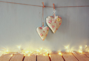 low key image of christmas image of fabric hearts hanging on rope in front of wooden background. retro filtered with glitter overlay
