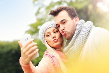Fototapete - Young romantic couple with smartphone in the park in autumn