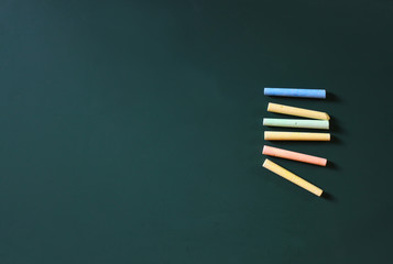 top view image of green chalkboard and collection of many chalks. room for text.