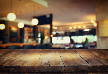 Canvas Prints Restaurant image of wooden table in front of abstract blurred background of restaurant lights