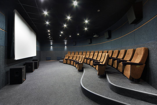 Interior of a small theater with orange chairs and screen