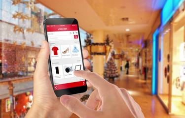 Smart phone online shopping in man hand during Christmas. Shopping center in background. Buy clothes shoes accessories with e commerce web site
