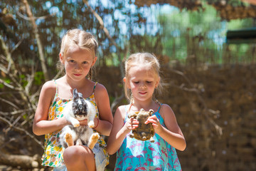 Little adorable girl with a land tortoise and cute rabbit at the