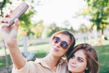 Beautiful girls taking self-portrait in the park