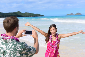 Man taking pictures with smartphone of beach woman