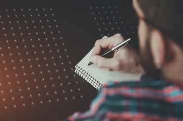 bearded man writing with pen in notebook