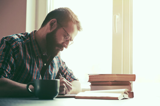 Bearded man writing with pen and reading books at table
