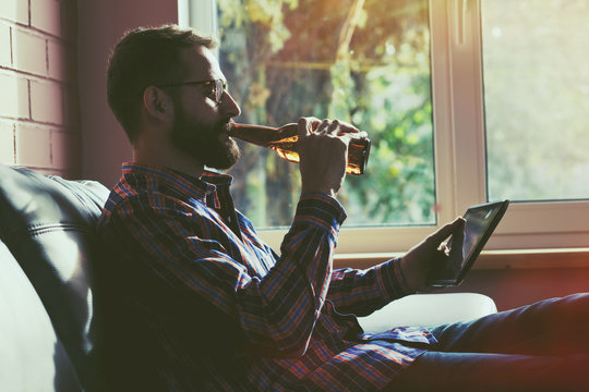 bearded man with digital tablet pc drinking bottle of beer