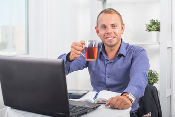 Businessman working in office, sitting at a table holding cup and looking straight.