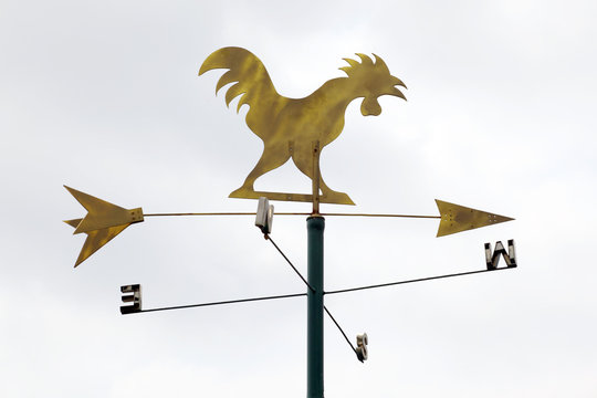 The golden metal weathervane over the white sky background.