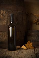 Still life with wine bottles, glasses and oak barrels.