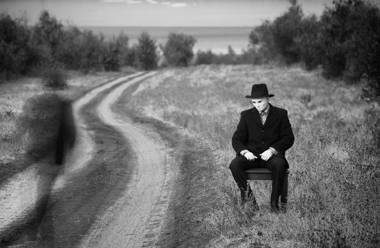 Man in the mask sitting on a chair by the side of the country road, black and white shot