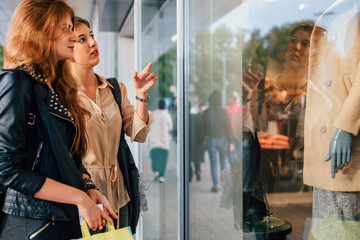 Two girls with shopping bags looking at clothes in a shop window