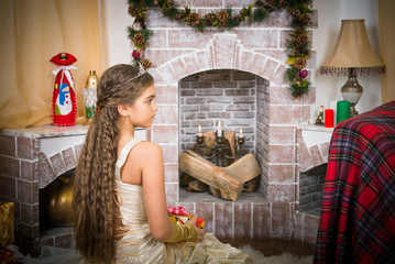 Girl with gift box near the fireplace, Christmas, New Year, family values. Beautiful girl with long hair in a gold dress waiting for gifts at Christmas