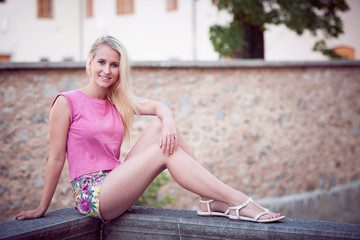 Beautiful young blonde woman resting on a bench at dusk in summer