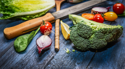 Fresh organic vegetables with kitchen knife on blue wooden background, close up