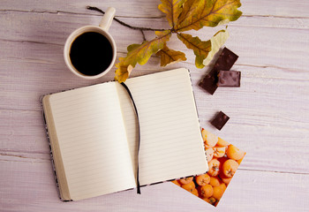 Autumn still life with  cup of coffee, notebook, leaves, chocolate and photo