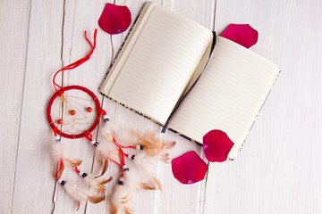 Still life with a blank notebook, dreamcatcher and rose petals