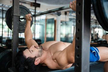 Handsome male bodybuilder doing bench press