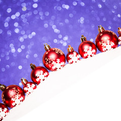 christmas red balls in snow on blue glitter background