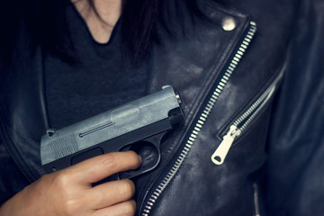 Woman with gun in hand, wore the black jacket texture background