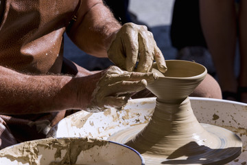 Potter shaping a bowl on a spinning wheel
