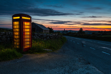 Red phone booth in English countryside at night