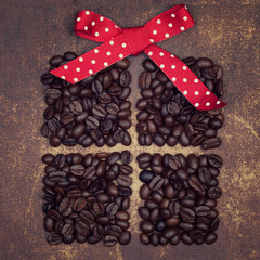 A red ribbon bow on top of a dark roasted coffee beans present o