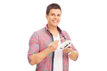 Young man eating sushi with Chinese sticks