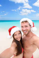 Christmas couple taking selfie on beach holidays