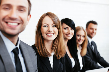 Young businesswoman sitting with business partners. Human resources concept