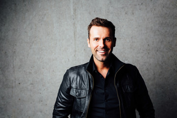 Happy handsome man in leather jacket looking at camera, standing against concrete wall