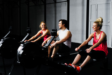 Friends training on rowing machine
