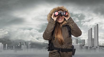 beautiful young woman hiker looking through binoculars