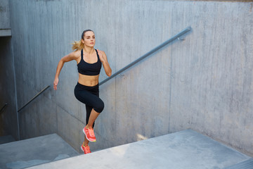 Athletic woman running up stairs