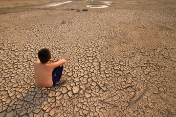Children sitting on cracked earth, Metaphor for Global warming and Climate change.