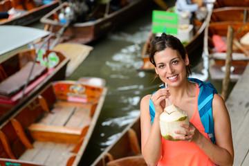 Happy female tourist visiting Damnoen Saduak floating market at Bangkok, Thailand. Woman on Asian travel drinking fresh coconut water.