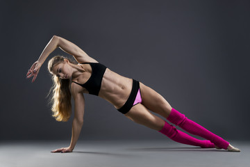 Beautiful muscular woman doing exercise side plank