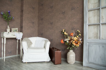 Interior retro room with an armchair, flowers, door and suitcase