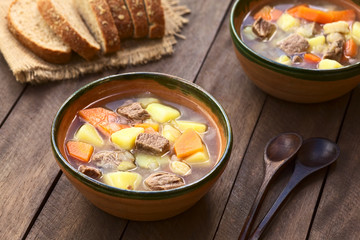 Traditional Hungarian soup called Gulyasleves made of beef, potato, carrot, onion, csipetke (homemade pasta) (Selective Focus, Focus in the middle of the soup in the first bowl)