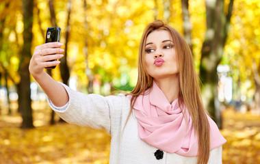woman taking duckface selfie in autumn city park