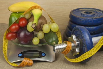 Chrome dumbbells surrounded with healthy fruits and vegetables on a table. Concept of healthy eating and weight loss. Diet for athletes.