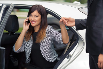 Smiling young businesswoman getting out of a car and talking on the phone