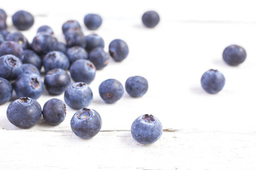 blueberries shot front on on white wooden boards