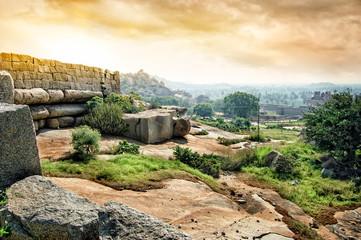 Fototapete - Ancient ruins of Vijayanagara Empire in Hampi at sunset sky, Karnataka, India.