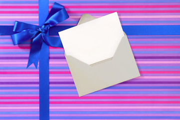 Blue gift ribbon bow on candy stripe wrapping paper, blank Chris