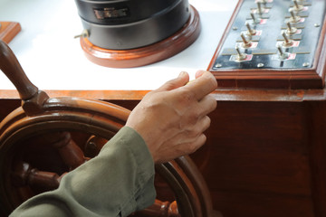 close up of man's Hands hold steering wheel the boat on daytime
