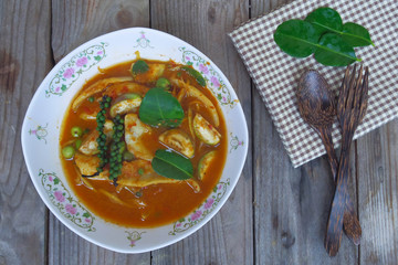 Spicy fish curry in bowl with fork and spoon