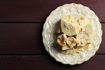 White chocolate pieces with nuts on plate, on color wooden background